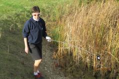 A golfer retrieves a ball from a water hazard