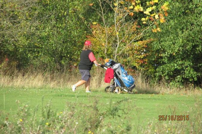 A golfer searching for a ball in long grass